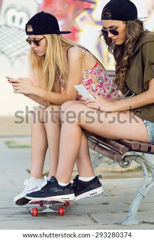 Portrait of beautiful young women using mobile phone in the street.