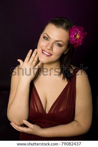 portrait of beauty big woman in red dress and with flower in her hair - stock photo