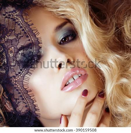 Portrait of beauty blond young woman through black lace close up sensual seduction - stock photo