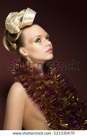 portrait of beauty blonde woman with creative golden make-up, ribbon in the hairdo and sparkly tinsel on nude shoulders. On red background