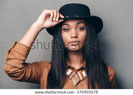 Portrait of beauty. Portrait of beautiful young African woman adjusting her hat and looking at camera while standing against grey background - stock photo