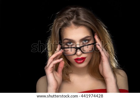 portrait of beauty woman in glasses with red lips looking at the camera in studio on black background