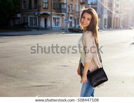 Portrait of beauty woman with perfect smile walking on the street and looking at camera