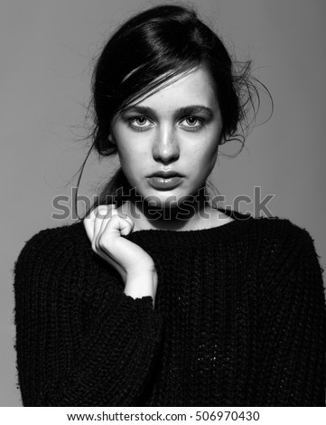 Portrait of beauty young brunette woman portrait in black fashion female pullover on gray background