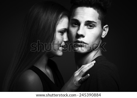 Portrait of beauty young couple against dark grey background - stock photo