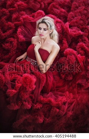 Portrait of beauty young woman in red dress sitting - stock photo