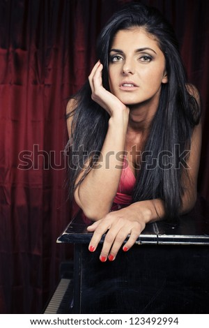 portrait of beauty young woman laying on piano - stock photo