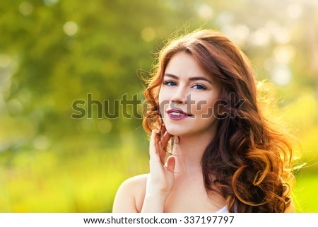 Portrait of beauty young woman with long hair in the sunlight