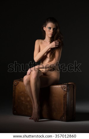 Portrait of beautyful naked posing blond woman sitting on leather suitcase, with long curly hair on black background - stock photo