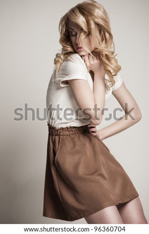 Portrait of beautyful posing blond woman with long curly hair - stock photo