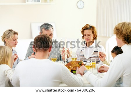 Portrait of big family sitting at festive table and holding each other by hands while praying - stock photo