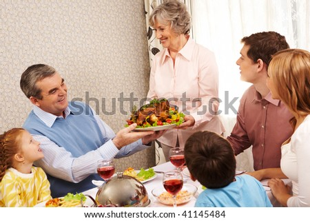Portrait of big family sitting at festive table and looking at aged female with dish of delicious turkey - stock photo