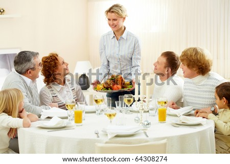 Portrait of big family sitting at festive table and looking at pretty woman with dish of roasted turkey - stock photo