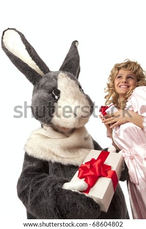 Portrait of big grey fur's color rabbit giving present to a pretty girl in pink dress against white background - stock photo