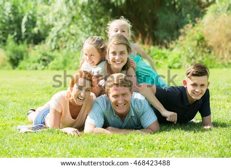 Portrait of big vigorous family with parents and four children lying together on green lawn outdoors