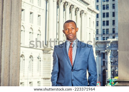 Portrait of Black Businessman. Dressing formally in blue suit, patterned undershirt, tie, short haircut, a young handsome black guy is standing in a business district, looking at you. - stock photo
