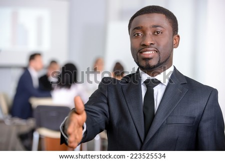 Portrait of black businessman, people group in background at modern bright office indoors - stock photo