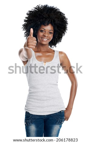 Portrait of black female with afro and casual clothing holding a thumbs up sign in studio