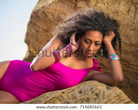 Portrait of black people, pretty happy young african american woman smiling. Rocks beach. Sexy girl in pink swimsuit and jewelry enjoying nature. Travel, holiday concept.