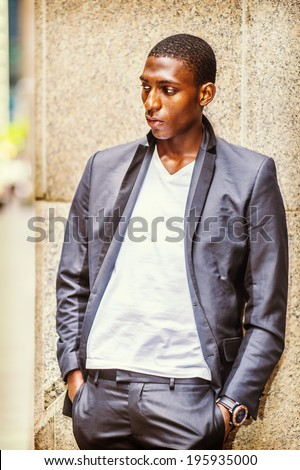 Portrait of Black Teenage Boy. Wearing a white under wear, fashionable jacket, a young black college student is standing back against a column, lost in thought. - stock photo