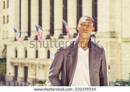 Portrait of Black Teenage Boy. Wearing a white under wear, fashionable jacket, a young black college student is standing in the front of an office building, sad, thinking, lost in thought. - stock photo