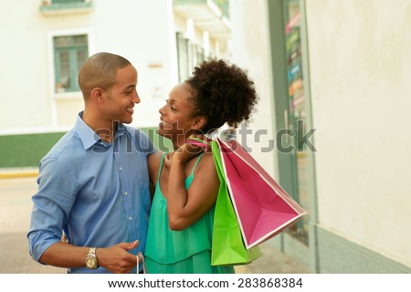 Portrait of black tourist heterosexual couple in Casco Antiguo - Panama City with shopping bags. The man and his girlfriend smile at the camera - stock photo