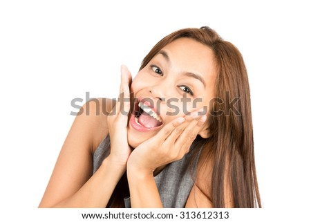 Portrait of blissful, euphoric Asian woman, light brown hair in sleeveless clothes, face cupped, head in hands reacting positively to happy news or information. Thai national of Chinese origin