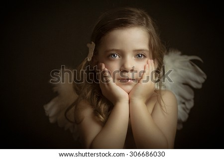 Portrait of blond, blue-eyed girl with angel wings in studio - stock photo
