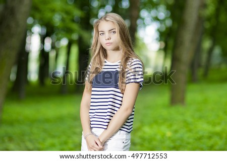 Portrait of Blond Caucasian Teenager Posing in Green Forest Outdoors.Horizontal Image Composition