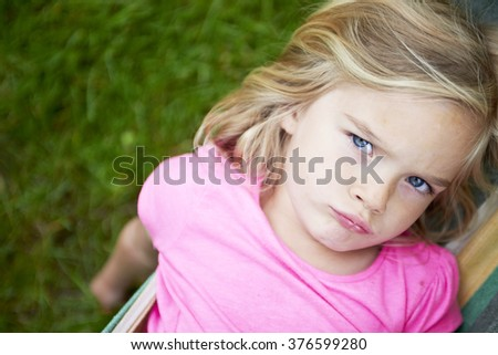 Portrait of blond child girl looking at camera with sad, upset face, relaxing on a colorful hammock in a home garden on summer holiday. Vacation lifestyle kid fun activities.