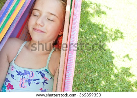 Portrait of blond child girl with closed eyes, smiling relaxing on colorful hammock in a home garden on a sunny summer holiday in swimming costume. Vacation lifestyle kid recreating fun activities. - stock photo
