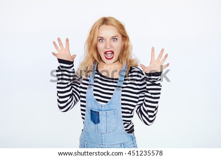 Portrait of blond girl acting like pussycat alluring over white background. Teenage girl scares you - stock photo