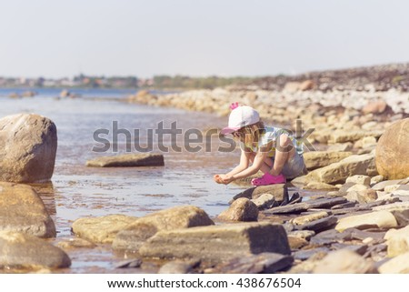 portrait of blond girl in preschool age sitting down with sea water on rocky and shallow coast in south sweden on sunny day and playing with water  - stock photo