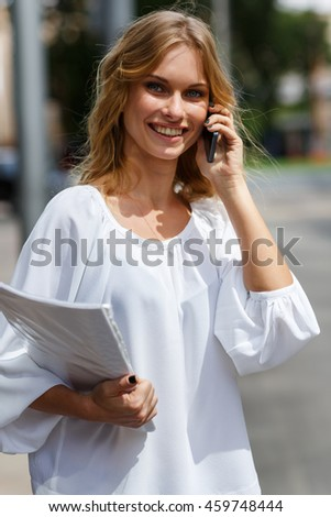 Portrait of blond girl talking on cellphone and holding contract