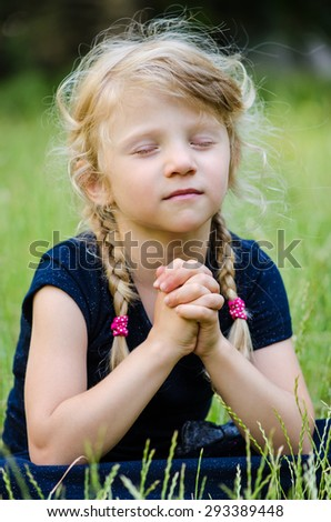 portrait of blond girl with braided hair praying - stock photo