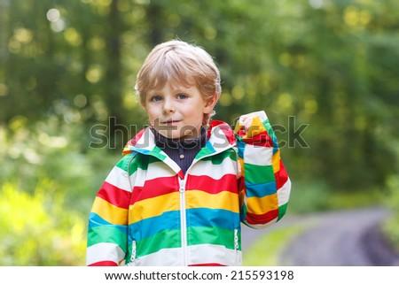 Portrait of blond little preschool  boy in colorful waterproof raincoat in autumn forest - stock photo