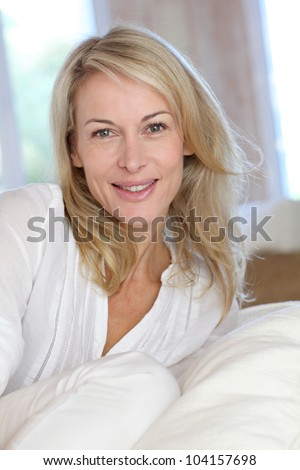 Portrait of blond mature woman relaxing in sofa - stock photo