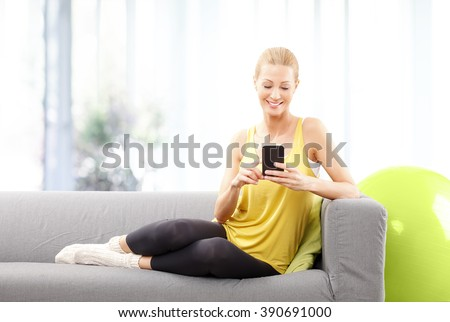 Portrait of blond mature woman using her mobile phone while sitting at home after fitness workout. - stock photo