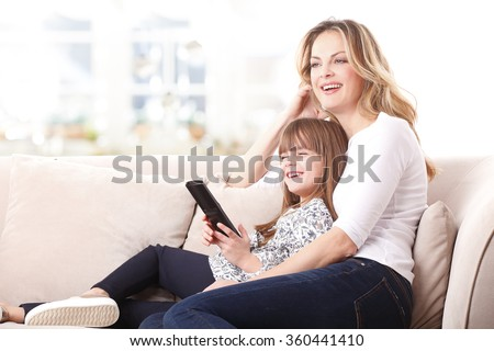 Portrait of blond mother and her cute daughter watching tv together at home. Little kid holding in her hand a remote controll while sitting next to her mom at sofa in living room.  - stock photo