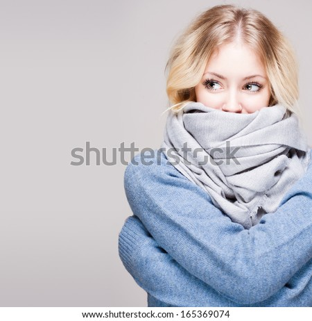 Portrait of blond winter beauty in light blue sweater and scarf. - stock photo