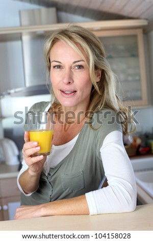 Portrait of blond woman in kitchen drinking orange juice - stock photo