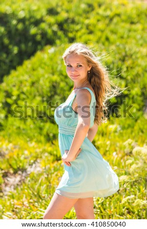 portrait of blond woman in mint-colored dress outdoor - stock photo