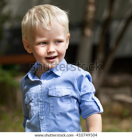 Portrait of blonde baby boy in summer street, outdoors - stock photo