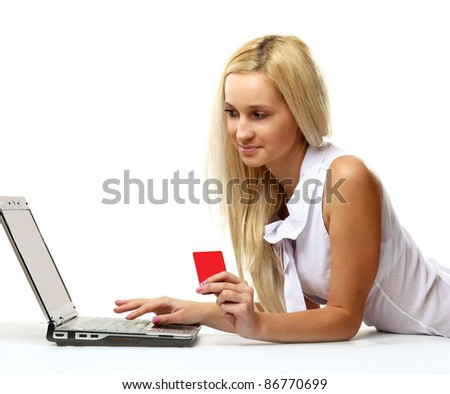 Portrait of blonde businesswoman lying on floor with laptop and credit card isolated