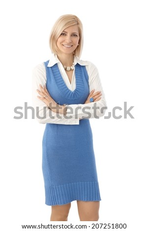 Portrait of blonde, casual female office worker standing with arms crossed, looking at camera, white background. Looking at camera smiling. - stock photo