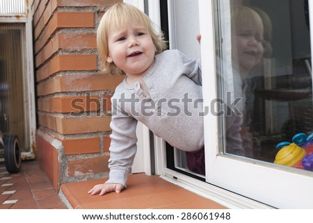 portrait of blonde caucasian baby nineteen month age chubby face calling peering terrace floor supported on the arms - stock photo