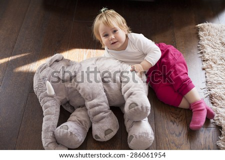 portrait of blonde caucasian baby nineteen month age looking at camera smiling with cheerful expression face together grey plush doll on brown wooden floor - stock photo