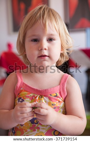 portrait of blonde caucasian baby two years old age chubby face looking at camera with serious expression wearing a flower colorful dress or summer shirt with a crayon in hands - stock photo