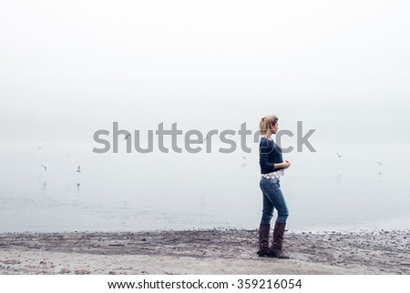 Portrait of blonde girl on riverside with birds and fog.