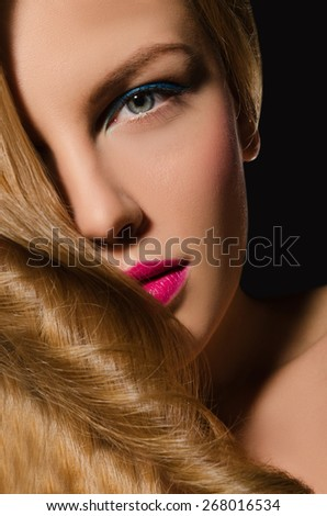 Portrait of blonde girl with beautiful hair on dark background - stock photo
